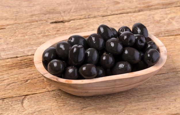 Die schwarzen oliven in der schüssel auf hölzernem hintergrund.
