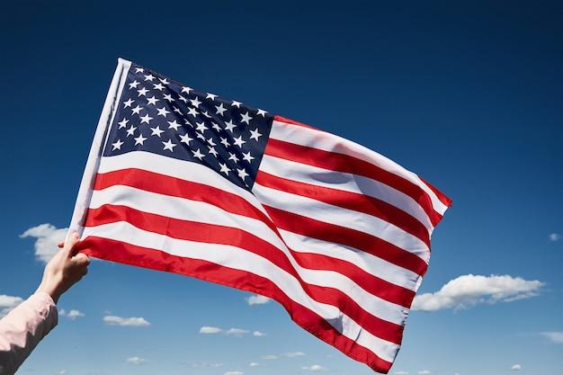 Die schwenkende amerikanische flagge im freien hält die us-nationalflagge gegen den blauen bewölkten himmel am unabhängigkeitstag im juli
