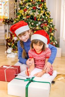 Die schwestern schreiben einen brief an den weihnachtsmann. tiefenschärfe.