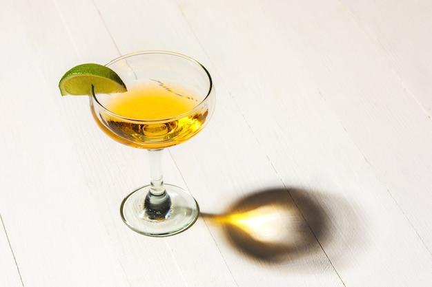 Die seite über dem bunten exotischen cocktail auf weißem holztisch im studio