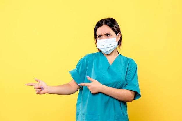 Die seitenansicht des arztes in einer maske spricht über die bedeutung des händewaschens