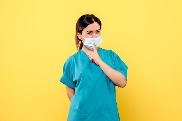 Die seitenansicht des arztes zeigt auf die medizinische maske