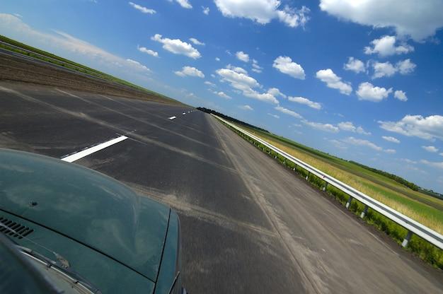 Die seitenansicht einer autoansicht ist eine glatte autobahn, umgeben von schöner sommernatur mit feldern, grünen bäumen und blauem himmel an einem sonnigen heißen sommertag. konzept für eine landreise
