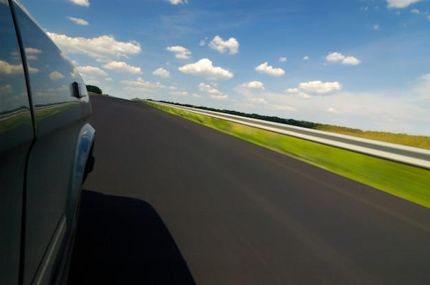 Die seitenansicht einer autoansicht ist eine glatte autobahn, umgeben von wunderschöner sommernatur