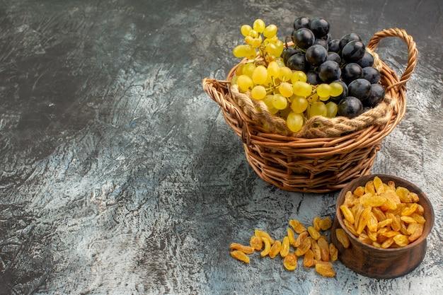 Die seitliche nahaufnahme trägt den korb mit den appetitlichen trauben neben der schüssel mit getrockneten früchten