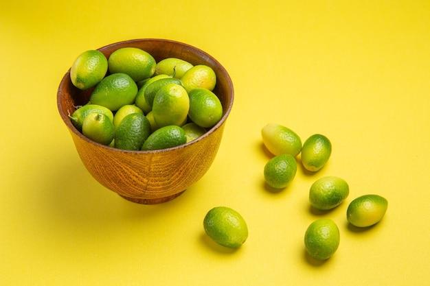 Die seitliche nahaufnahme trägt die appetitlichen grünen früchte neben der schüssel auf der gelben oberfläche