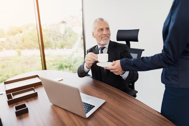 Die sekretärin brachte ihrem chef eine tasse kaffee.