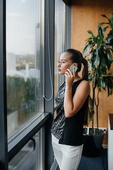 Die sekretärin telefoniert neben dem fenster im büro