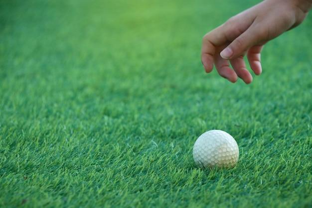 Die selektive fokushand des kindercaddys greift nach dem golfball auf grün. um das ziel weiter zu erreichen
