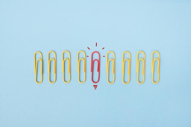 Die separate büroklammer wird als glühbirne als symbol für innovatives denken rot hervorgehoben.