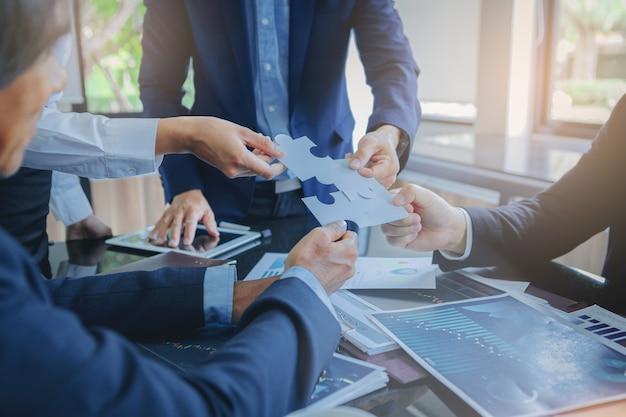 Die setzenden geschäftsleute schließen puzzlen an. teamarbeit und strategische lösung. ausgewählter fokus