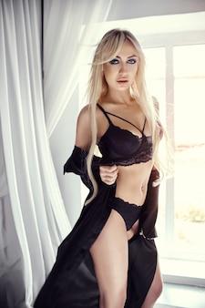Die sexy blondine in schwarzer unterwäsche und high heels steht am fenster
