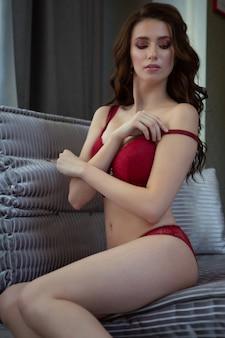 Die sexy brünette glättet den riemen der roten unterwäsche von lacy, die auf einem luxuriösen stuhl sitzt