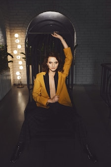 Die sexy junge frau im gelben blazer am nackten körper und in trendigen karierten hosen sitzt auf einem metallstuhl und posiert im dunklen innenraum
