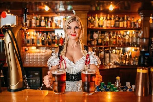 Die sexy kellnerin hält zwei tassen frisches bier an der theke in der kneipe.