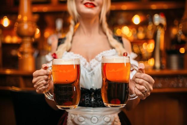 Die sexy kellnerin hält zwei tassen frisches bier in der kneipe.