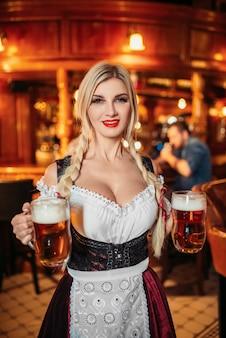 Die sexy kellnerin hält zwei tassen frisches bier in der kneipe