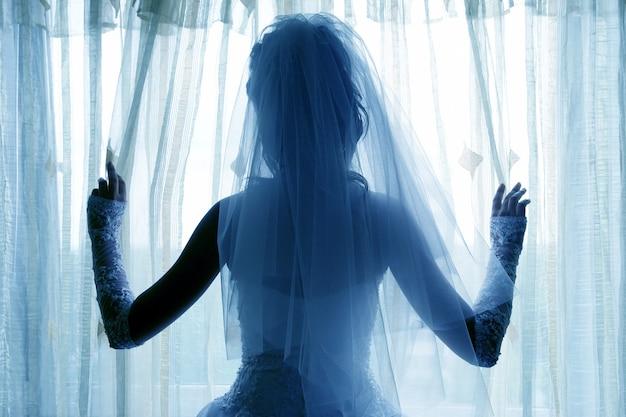 Die silhouette der braut, die nahe dem fenster steht. mode und schönheit der festlichen kleidung