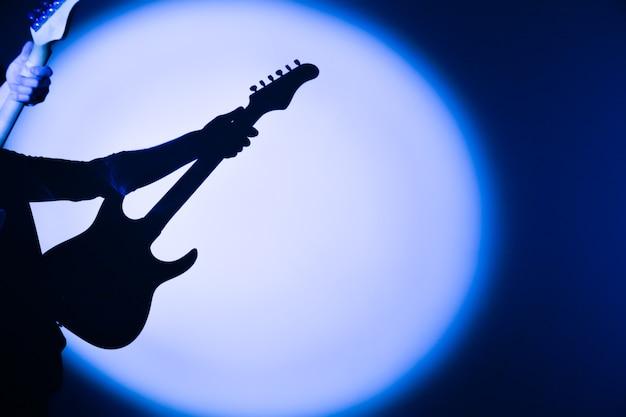 Die silhouette der e-gitarre im schatten. mann, der musikinstrument hält musiker im rampenlicht. kreativer stil mit hellen schatten.