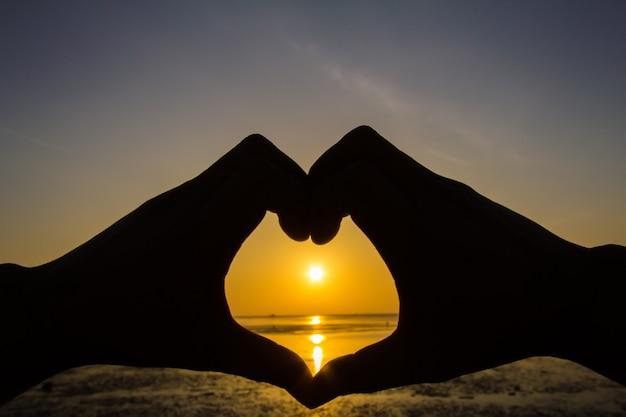 Die silhouette der hand eines mannes in einem wunderschönen sonnenaufgang fängt die sonne im herzen ein.