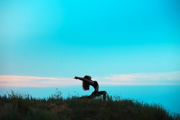 Die silhouette der jungen frau praktiziert yoga
