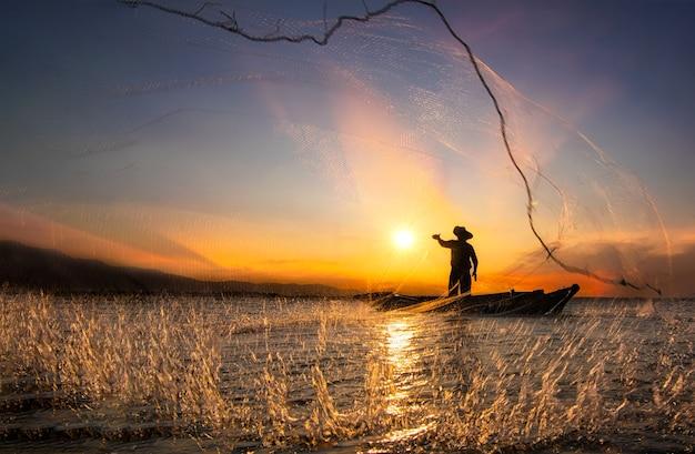 Die silhouette des fischers wirft fischernetze, um den fisch zu finden