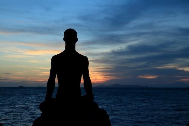 Die silhouette des perfekten körpermannes wirkt yoga auf dem felsen mit meeressonnenuntergangsraum