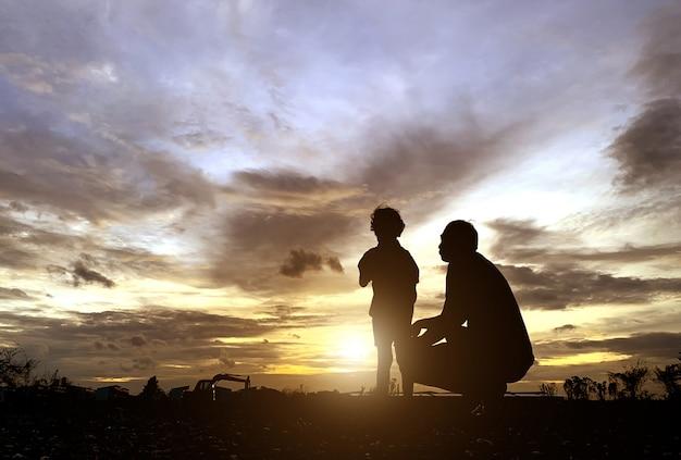 Die silhouette des vaters und des sohnes, die den sonnenuntergang für vatertagsliebesfeiertagskonzept genossen