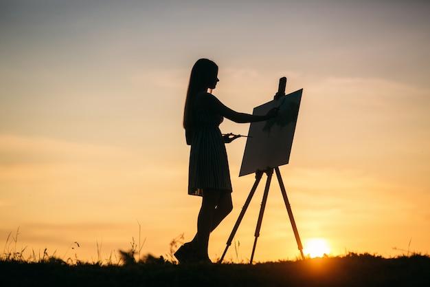 Die silhouette einer blonden künstlerin malt ein gemälde auf die leinwand