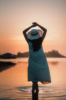 Die silhouette einer frau bei sonnenuntergang silhouette einer rückansicht einer jungen frau in einem strohhut mit h...