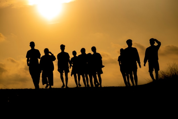 Die silhouette einer gruppe von menschen feiert erfolge auf dem hügel.