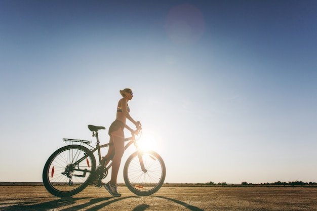 Die silhouette einer starken frau in einem bunten anzug, die in einer wüstengegend auf einem fahrrad sitzt. fitness-konzept.