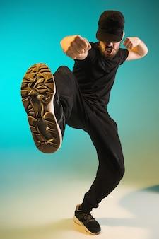 Die silhouette eines jungen hip-hop-männer breakdancer tanzt auf buntem hintergrund
