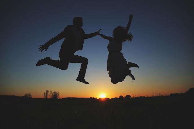 Die silhouette eines jungen paares springt und hat am sommerabend spaß draußen auf dem feld