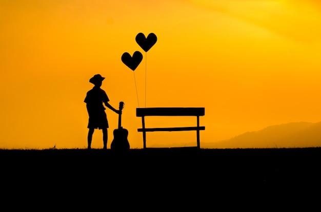 Die silhouette eines jungen stand neben einem stuhl, allein. sonnenuntergang