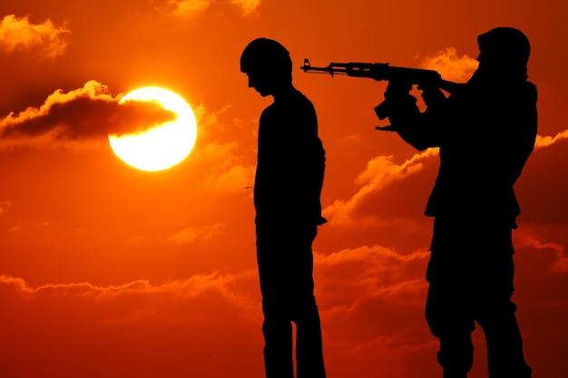 Die silhouette eines mannes mit gewehr zeigte auf den rücken des opfers