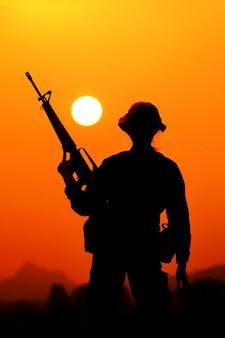 Die silhouette eines militärsoldaten mit der sonne als marine corps für militärische operationen