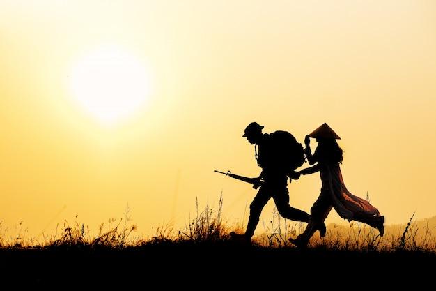 Die silhouette eines soldaten, der eine junge frau führte, um dem krieg zu entkommen