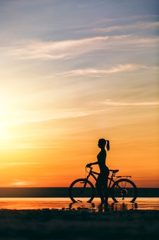 Die silhouette eines sportlichen mädchens in einem anzug, das an einem warmen sommertag bei sonnenuntergang auf einem fahrrad im wasser sitzt. fitness-konzept.