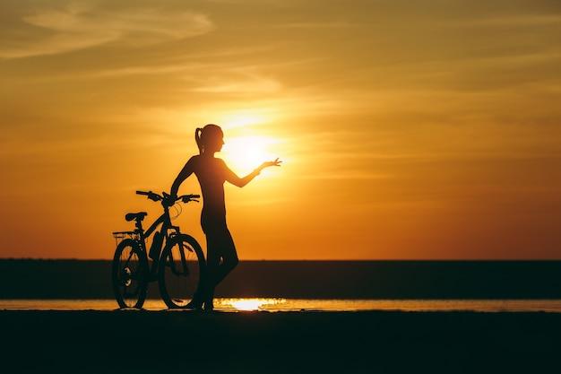 Die silhouette eines sportlichen mädchens in einem anzug, das neben einem fahrrad im wasser steht und ihre hand bei sonnenuntergang an einem warmen sommertag in die ferne zeigt. fitness-konzept.