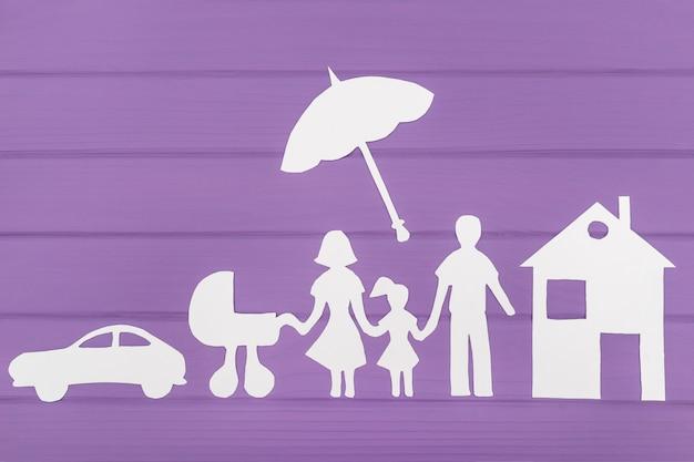 Die silhouetten aus papier von mann und frau mit zwei mädchen unter dem regenschirm, haus und auto in der nähe geschnitten