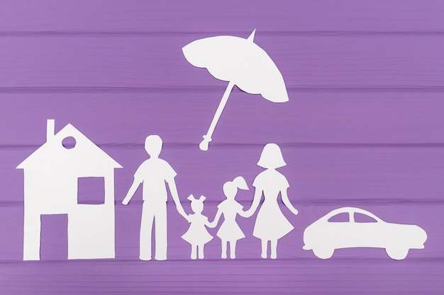 Die silhouetten aus papier von mann und frau mit zwei mädchen unter dem regenschirm, haus und auto in der nähe