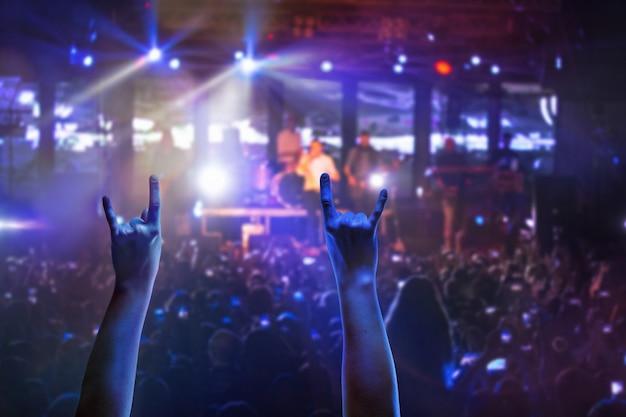 Die silhouetten des konzertpublikums vor hellen bühnenlichtern. konzert einer abstrakten rockband