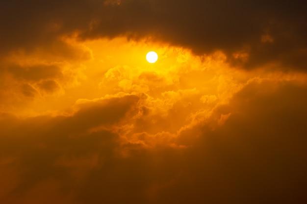 Die sonne auf dramatischem wolkigen orangefarbenen himmelsnaturhintergrund