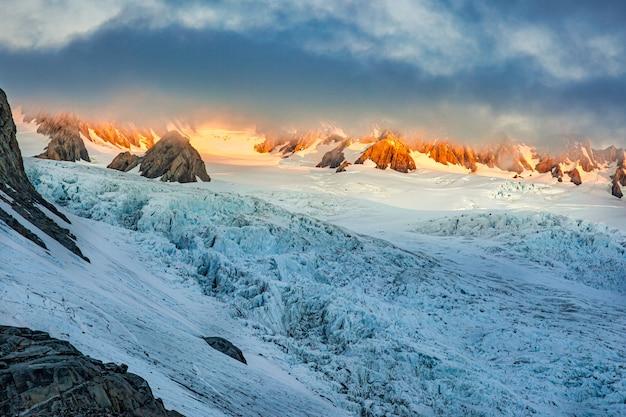 Die sonne bricht durch die dicke wolke an der spitze des gletschers in den südlichen alpengipfeln