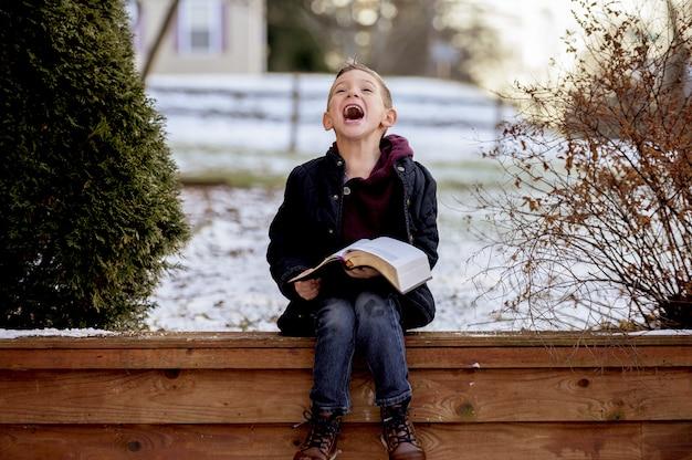 Die sonne geht über einem niedlichen kleinen jungen auf, der die bibel mitten in einem winterpark liest