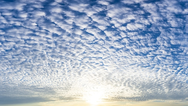 Die sonne und die flauschigen weißen wolken voll am blauen himmel, naturphänomenbild.