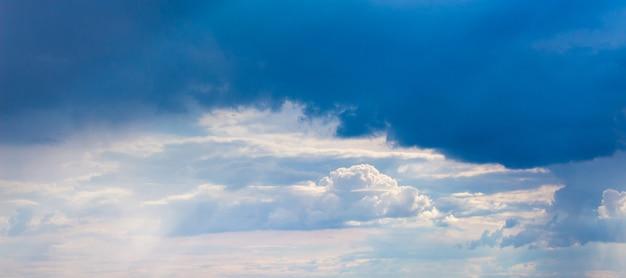 Die sonnenstrahlen dringen durch eine dunkle wolke in den gewitterhimmel