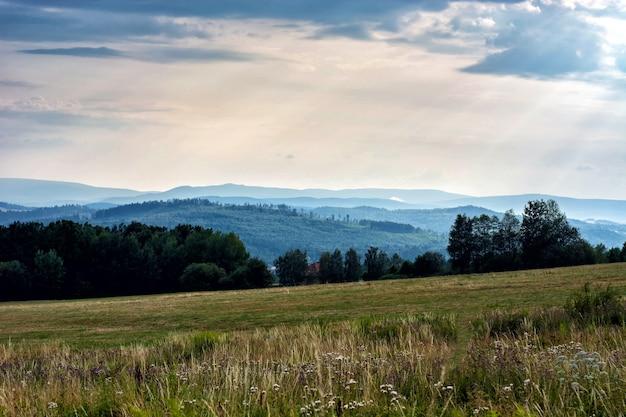 Die sonnenstrahlen wandern von den wolken zu den berggipfeln.