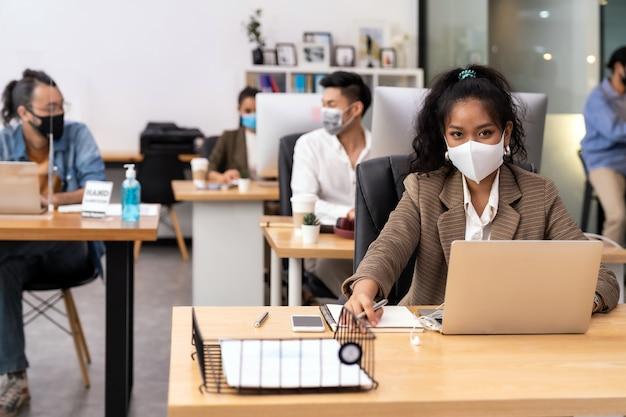 Die soziale distanz im büro mit dem business-team, das gesichtsmasken trägt